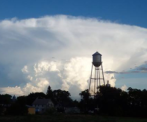 Water tower with thunderhead behind it